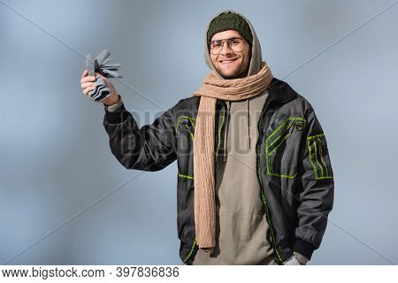 Man In Parka Holding Gloves And Smiling On Grey