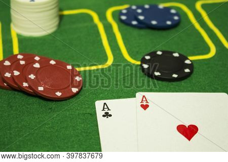 Two Cards - A Black Clubs Ace And A Red Hearts Ace - With Diverse Colored Chips At A Green Poker Tab