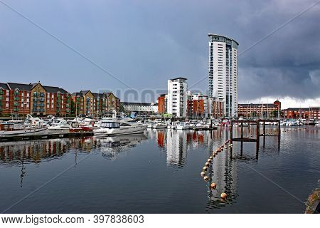 Buildings Reflected In The Water Of Swansea Marina, Wales