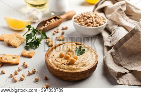 Hummus In A Wooden Plate With Parsley And Croutons. Dishes Of Chickpeas, A Vegetarian Dish.