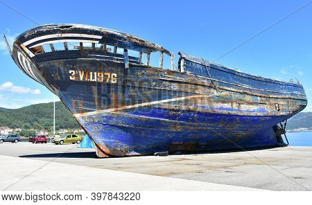 Muros, Spain, Aug 23, 2020. Old Blue Ruined Wooden Galician Fishing Vessel In A Harbor. Rias Baixas,