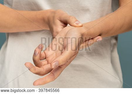 Closeup Of Woman Arms Holding Her Painful Wrist Caused By Prolonged Work On The Computer, Laptop. Ca