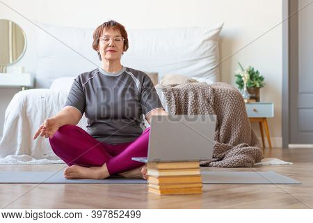 Senior Woman Meditates At Home In A Lotus Position In Front Of A Laptop Monitor. The Concept Of A He