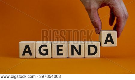 Agenda Symbol. Concept Word 'agenda' On Cubes On A Beautiful Orange Background. Male Hand. Business