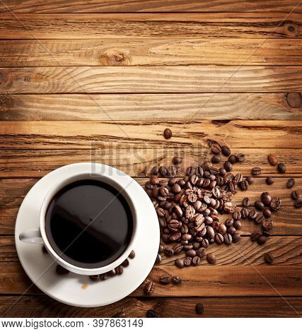Coffee Cup With Roasted Coffee Beans On A Brown Wooden Table Background With Coffee Beans Scattered