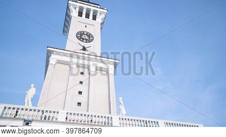 White Clock Tower On Background Of Blue Sky. Action. Bottom View Of Beautiful White Clock Tower On B