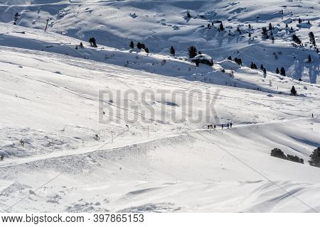 Winter In The Mountains. Skiers On A Piste In The Swiss Alps, 4 Valleys