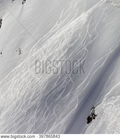Snowy Off-piste Ski Slope With Traces From Skis And Snowboards At Sunny Winter Evening