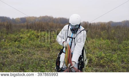 Man Carries Parachute. Action. Man Carries Multi-colored Parachute After Landing. Man In Overalls Dr
