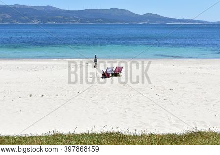 Beach Chairs And Umbrella On An Atlantic Ocean Beach With White Sand And Turquoise Water. Rias Baixa