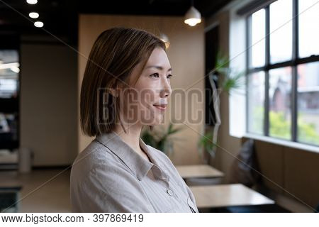 Asian woman looking out of window in creative office cafeteria. social distancing in business office workplace during covid 19 coronavirus pandemic.