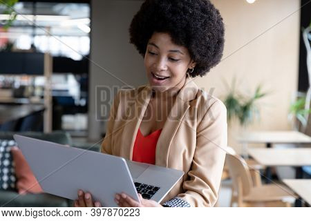 Smiling mixed race businesswoman using laptop during video call in office. technology and social distancing in business office workplace during covid 19 coronavirus pandemic.