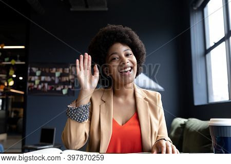 Smiling mixed race businesswoman during video call in creative office, waving. technology and social distancing in business office workplace during covid 19 coronavirus pandemic.