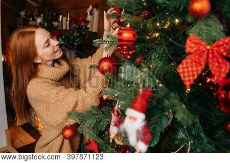 Cheerful Redhead Young Woman Decorating Christmas Tree With Holiday Ornament At Cozy Living Room Wit