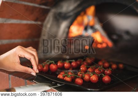 Mixed race female chef in kitchen. trainee chef standing at a furnace and preparing food.