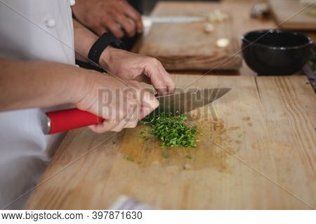 Female chef and mixed race male chef in kitchen. trainee chef and female chef standing at a table and preparing food.