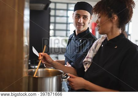 Two diverse male and female chefs in kitchen. trainee chefs standing at a table, wearing black aprons and preparing food.