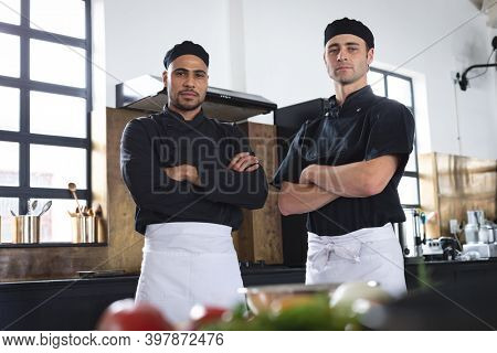 Two divserse male chefs in kitchen. portrait of two trainee chefs looking at camera with arms crossed.