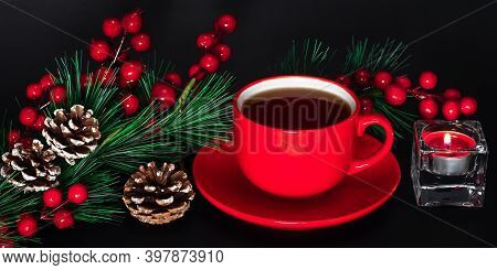 Red Ceramic Cup Of Coffee With Saucer And Christmas Decorations On Dark Background. Burning Candle,