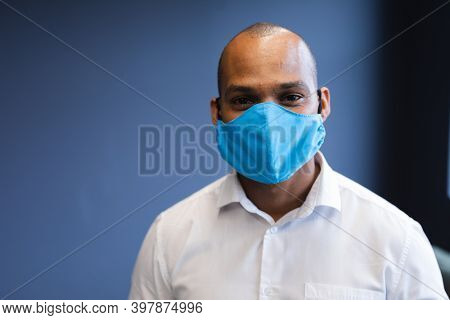 Portrait of mixed race businessman wearing face mask in office. social distancing in business office workplace during covid 19 coronavirus pandemic.