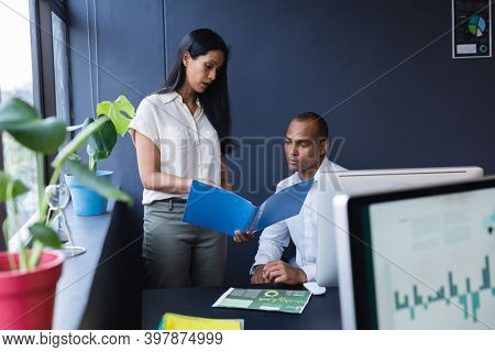 Mixed race man and woman working together in creative office, reading documents. modern office business teamwork interacting.