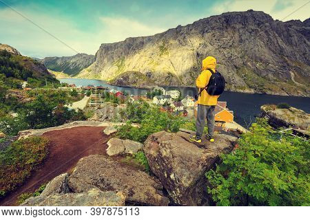 Panoramic View Of Fjord And Fishing Village. Man Tourist With Standing On A Cliff Of Rock And Lookin