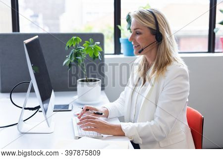 Caucasian woman wearing phone headset in modern office, using computer. communication and social distancing in business office workplace during covid 19 coronavirus pandemic.
