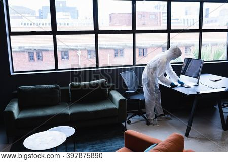Health worker in protective clothing disinfecting creative office. hygiene protection in business office workplace during covid 19 coronavirus pandemic.