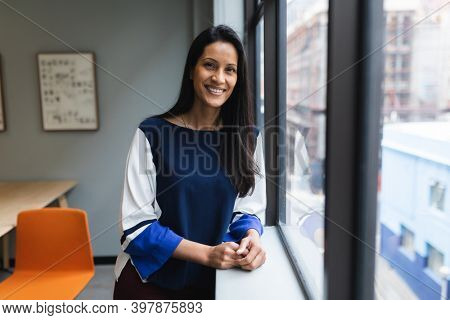 Portrait of mixed race woman by window in creative office. social distancing in business office workplace during covid 19 coronavirus pandemic.