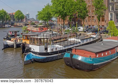 Amsterdam, Netherlands - May 16, 2018: Big House Boats Moored At Canal In Amsterdam, Holland.