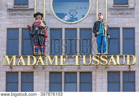 Amsterdam, Netherlands - May 15, 2018: Madame Tussaud Museum Sign And Two Statues At Building In Ams