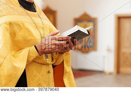 Orthodox Church. Christianity. Priest Hands Holding Holy Bible Book In Traditional Orthodox Church B