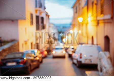 Abstract Blurred Boke Bokeh Background Of European Town Street In Evening Sunset Or Sunrise Time. Ma