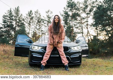Cheerful Girl In Tracksuit Stands In Front Of The Car