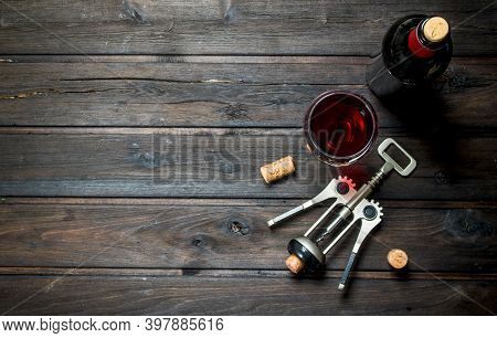Wine Background. Red Wine With Corkscrew. On A Wooden Background.