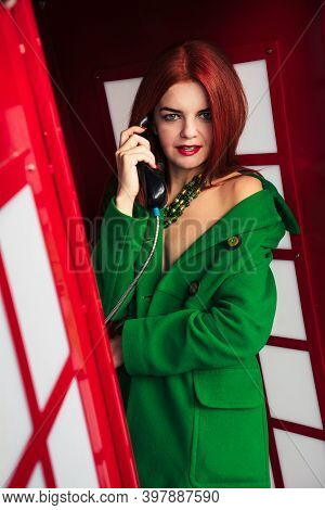 Redhead Girl In A Green Coat Talking On The Phone In A Red Phone Booth 3