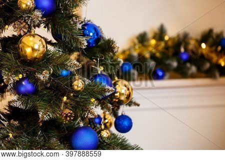 Decorated Christmas Tree Close-up. Blue And Gold Balls And Garland Lights. Christmas Balls On The Tr