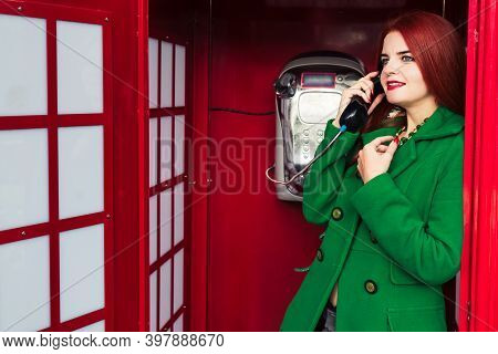 Redhead Girl In A Green Coat Talking On The Phone In A Red Phone Booth 1