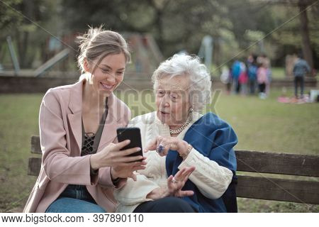 granddaughter explains to grandmother how to use a smartphone