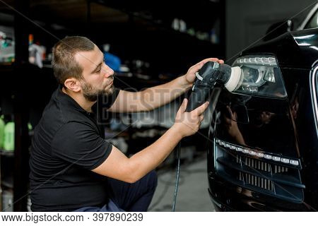 Close Up Of Professional Caucasian Male Auto Service Worker, Waxing And Polishing Headlight Of Black