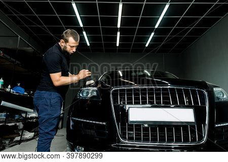 Car Detailing And Polishing Concept. Professional Caucasian Male Car Service Worker, Holding In Hand