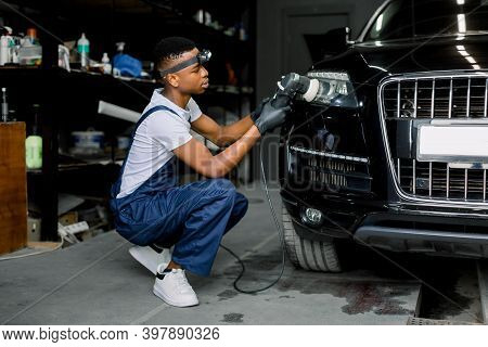 Detailing And Polishing Of Car Headlights. Young Professional Concentrated African Male Worker With