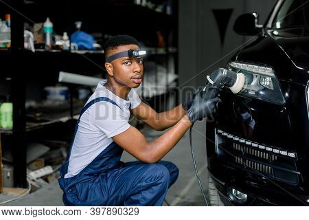 Young Handsome African Man, Worker Of Auto Detailing Service, Holds A Polisher In The Hand And Polis