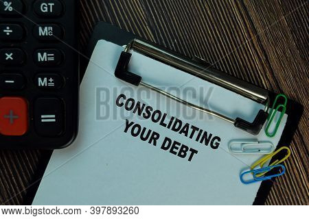 Consolidating Your Debt Write On A Paperwork Isolated On Wooden Table. Finance Concept