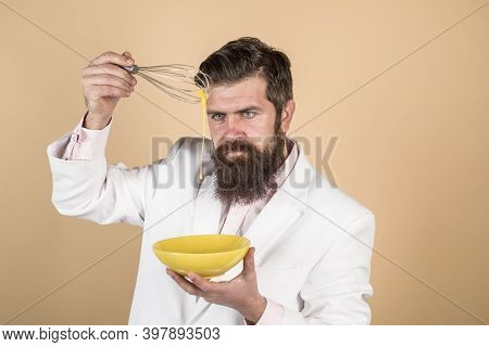 Handsome Bearded Man Preparing Eggs For Breakfast. Bearded Man With Bowl And Egg Whisk. Kitchen Tool