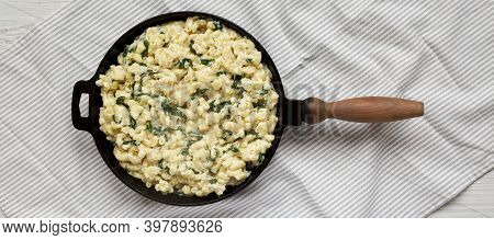 Homemade Spinach Mac And Cheese In A Cast-iron Pan On Cloth, Top View. Flat Lay, Overhead, From Abov