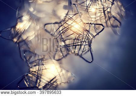 Christmas Luminous Garland In The Shape Of Stars From Led Bulbs. Glowing Stars Made Of Wire Close-up