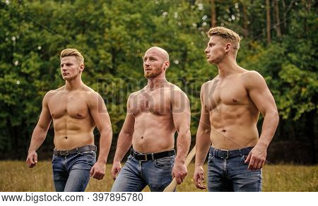 Strong Men Nature Background. Inspiring Training Harder. Group Muscular Men With Axe. Athletic Man U