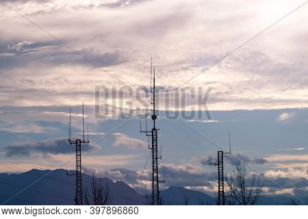 Three Telecommunication Masts Or Mobile Towers With Satellite Antennas Silhouettes At The Sunset Clu