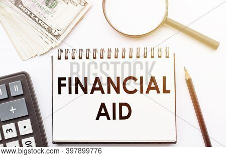 Financial Aid - Text Written On A Notebook With Office Background